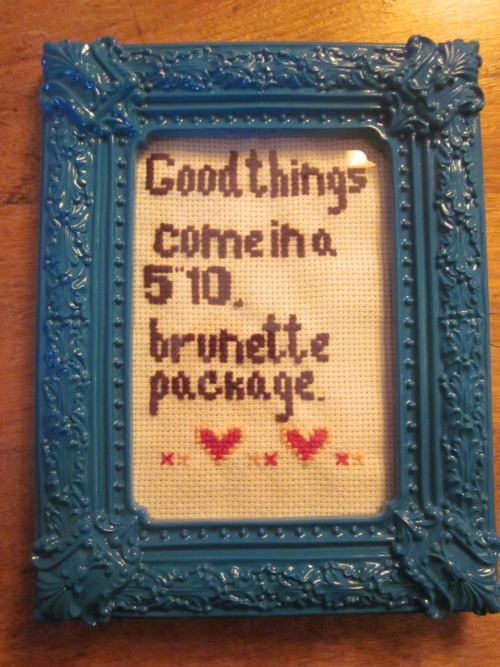 "[image description: a handmade cross stitch in an ornate turquoise frame. it reads ""Good things come in a 5'10"" brunette package"" with little hearts at the bottom] cross stitch by annemarie. sexy tall femme solidarity!"