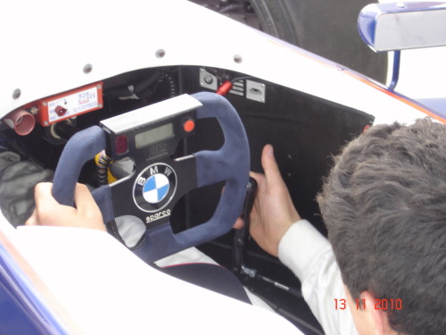 From the cockpit:  As a Formula BMW driver, I am required to wear: Nomex Underclothing (Pants and Long-Sleeved Vest) a Puma Triple-Layer Nomex Racing Suit Nomex Socks Puma Nomex Gloves and Boots a Nomex Balaclava my Custom-Painted, Nomex-Lined Arai GP-6 Racing Helmet; and a HANS device. Nomex is the name for the fire-retardant material racing drivers use to protect themselves in the case of an accident. As you can imagine, wearing all this Nomex on a hot day could get very, well…hot. And when you sweat in Nomex…it becomes itchy. The HANS device is the neckbrace that single-seater racing drivers use. The seat straps go over the device on your shoulders and the device connects to the sides of your helmet to reduce whiplash in an accident. I have never felt so claustrophobic - yet more at home - as when I have been strapped into a Formula BMW. The seat-straps and HANS device restrict your movement to the point where you can only move your arms and your head about 30 degrees to each side - just enough to be able to see your rear-view mirror. After having exerted themselves to the point where they are red in the face and their is sweat pouring into their eyes; the mechanic who is tightening your belt will ask if you are still able to breathe. If you answer yes, he will proceed to tighten you belts until breathing literally becomes painful. There is hardly any space to move your feet - as you can see by the photos of the pedals - and it can get very uncomfortable if a part of your body becomes unbearably itchy - such as when you sweat while wearing Nomex… The driver's view is limited to pretty much the piece of road in front of him due to the low-ride height of the car. To put things into perspective; only about 30% of the top of the front tyre can be seen by the driver when he is strapped in. However, all this is forgotten the second you dump the clutch and floor the accelerator. The concentration required for perfect braking, cornering, gearing and throttle control takes over any other worry or irritation which may be residing at the front of your mind. That is why I love racing. There are no worries. Other than, of course: DON'T CRASH!