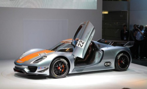LIVE from Detroit: In its second showing of its hybrid-powered supercar, the 918 Spyder, Porsche  has gone from the street directly to the track. Instead of showing the  rumored road-going coupe version of this high-end two seater, Porsche  has infused this mid-engine V-8 hybrid exotic with a racing pedigree by  transplanting the flywheel energy storage system from the 911 GT3 Hybrid racer to supplant the open car's lithium ion battery pack, taking performance to even higher levels.