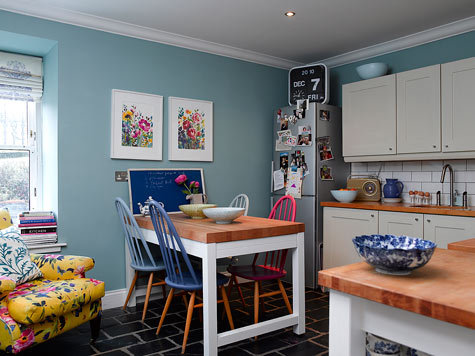 Lots of my favourites on display here!   Farrow & Ball Dix Blue? Check.  Habitat flip clock? Check.  Painted chairs? Check.  Floral armchair? Check.  Metro tiles? Check.  Little flower paintings? Check.  Ermm… can I move in please, Fiona Douglas?