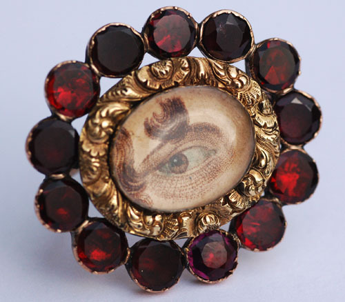 ornamentedbeing:  Georgian eye miniature brooch, circa 1820, watercolour on card, set to a gold frame with flat-cut garnet surround and under crystal. Immaculate condition. For similar eye miniature, see Royal Collections, Stockholm, [hair bracelet circa 1820, with eye miniature].