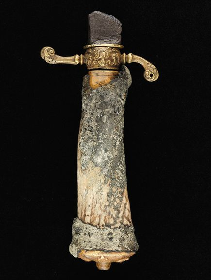 Mid-17th to early 18th Century sword found on the Queen Anne's Revenge, the ship of the infamous pirate Blackbeard, wrecked off the Outer Banks of North Carolina (US). Edward Teach (var. Thatch) claimed a French slave ship, the Concorde,which he renamed as the Queen Anne's Revenge.These are the reconstructed remains, as the artifact is in several pieces. The gold quillon (the crossbar of the hilt) originally had some form of chain or strap that connected to the pommel. The hilt is carved from antler, which could perhaps reveal a more specific region of production. The pommel (pictured below) has what appear to be faces and fleurs-de-lis, the latter of which are symbols of French royalty. This could be further evidence of the sword's country of origin, as it may not have necessarily been on the ship before Blackbeard.  (Photographs courtesy Wendy M. Welsh, North Carolina Department of Cultural Resources)