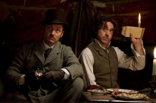"According to Jude Law, who returns as Watson in Guy Ritchie's currently filming Sherlock Holmes 2, one of the most exciting things in the sequel is the ""fear level."" ""We get pretty kicked around,"" Law said. ""Just look at the state of us."" You can see the state of Law and his co-star Robert Downey Jr. in the above below, the latest look at the film scheduled for release December 16. Both he and Downey spoke to the Los Angeles Times about the film, which is set one year after the original. The piece also details several action scenes which I'd consider minor spoilers. The first features Watson, Holmes and a gypsy woman named Sim running away from gunfire in a train yard. Finding cover, they all fumble for guns, but Sim gets hers out first and blasts the bad guys. Sim, of course, is played by Noomi Rapace, the original Girl With the Dragon Tattoo. The second scene, which seems like it's just another shot from the same train yard chase, features Holmes and Watson taking cover from behind a crate. Watson then jumps up with an almost Gatling gun and lays waste to everything around them. Plot of second Sherlock Holmes: Set in 1891 — a year after the last film's events — the sequel shows Holmes continuing his pursuit of Professor Moriarty (played by Jared Harris), who, if the investigator's instincts are correct, might be the world's first supervillain. Watson, meanwhile, is still trying to be a good partner to his love, Mary Morstan (Kelly Reilly), while keeping Sherlock alive.  I absolutely can't wait for the second film! I really enjoyed Downey Jr as Sherlock and of course Law as Watson. What do you guys think?"