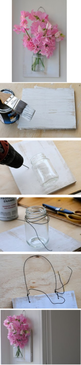 Making a vase for on the wall…   step one Buy  or find a piece of wood to use that is in proportion to the jar, which  you also need to find or buy. If you are like me you will have the  chance to recycle one. Make sure the jar (or use a vase) has a lip on  the top. Paint the wood however you would like it. step two Position the jar on the wood and drill two holes on either side at the the base of the opening.  step three Wrap  steel wire around the lip of the jar a few times and twist it once   until it's secure.  Position the jar so that it's lined up on the wood   and poke the ends through the small holes that you drilled.  Wrap them   together in the back and clip any extra wire. step four Drill  two additional holes at the top of the wood and wrap a second  piece of  steel wire through leaving a large loop at the top.  Twist the  ends  around the base and clip off the extra wire. Add water and flowers then hang it up.  Dried or imitation flowers could also be used. It really was that simple! Fun to make :)