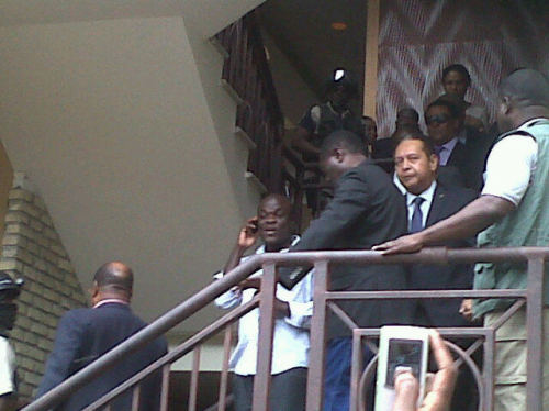 """Baby Doc"" Duvalier has been taken from his hotel. Here's a photo from Twitter of the former Haitian leader being escorted. Unclear if he was arrested or not yet. Big news, kids. (via Twitter user etiennecp)"