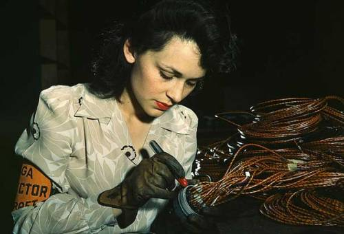 Working on Aircraft: An aircraft worker checks electrical assemblies while wearing a polynesian printed uniform jumpsuit.