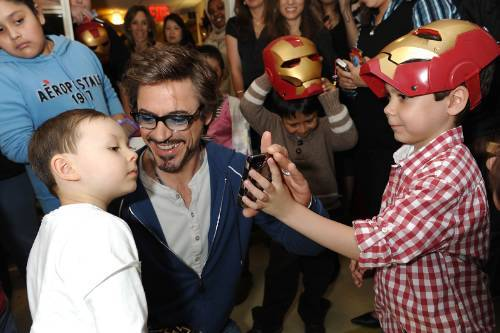 "Dear RDJ (Robert Downey Jr. for the newbies), I had the recent pleasure of meeting you a little over a week ago. Since then, I have enjoyed your newest film Iron Man 2. One of the many things I love about living in NYC is being able to bump into talented individuals such as yourself. You came to my work to hang out with kids who have cancer and I figured you would be in, get your pics, and out in 15 minutes. Surprisingly, you stayed for over an hour and made sure each kid got a pic, signature, and personal interaction with the real Iron Man. One kid exclaimed, ""He's (Iron Man) real."" I must admit I reflect the same sentiment, you're real, a real grounded and engaging person. The staff wouldn't admit it, but we were hanging around hoping we might get a chance to chat with you as well. Your handler lady said, ""Let's get one group staff picture."" You weren't having that. You said in your most authoritative Tony Stark voice, ""Now let me tell you how this is going to go. I want an individual picture with each and every one of you. Let's start a line and I'm going to begin with you (me!)."" You asked me my name and I managed to say it and you said, ""It's nice to meet you, Katie."" The professional photographer snapped a picture of us and I said ""Can I get a copy of that?"" You said, ""Make sure she gets a copy of that and bill it to Paramount.""  — from Katie, who met RDJ in May 2010 when he visited the Stephen D. Hassenfeld Children's Center for Cancer & Blood Disorders in NYC (her open letter to RDJ; via Crushable)"