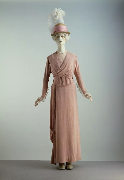 Promenade Suit | c. 1913 This garment reveals the fashionable elements of dress immediately before World War I (1914-1918). The line is straight and the cut (especially of the cross-over draped bodice) is intricate. Rows of non-functional tiny buttons were frequently used as decorative motifs in this period. The bodice is lined with white cotton (with ruffles attached to give fullness at the bust) and has a stiff, silk-faced waistband. It was not made by one of the top houses, for it is probably a copy by a good dressmaker of a Paris model .