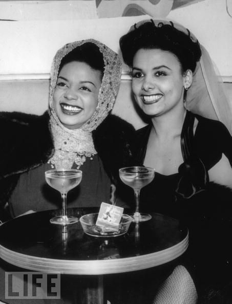 "Hazel Scott and Lena Horne enjoying a drink, circa 1940s or 1950s.   This photo is via LIFE magazine and the caption says this is ""circa 1934"" but that is wrong. Lena Horne was an unknown 17-year-old chorus girl in Harlem in 1934."