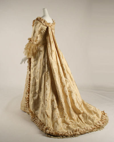 chocolatepot:  Reception gown (or costume), Mme Ed. E. Thomé, ca. 1880; silk Metropolitan Museum of Art 1998.271a, b; Gift of Richard Martin Victorian fashion always contained some kind of historicizing element, and in the 1880s fashion's focus was on the eighteenth century.  The pleats on the back of this dress are reminiscent of the sack back of a robe à la française, as are the lacy engageants; the pleated trim is a replica of that found on many historical gowns; and the compère front, with the appearance of a buttoned waistcoat, is also an historical touch.       How did I not know about this?! It's my two most-beloved periods in fashion history combined… I couldn't possibly ask for more! IT'S ABSOLUTELY STUNNING. One day when I get better at sewing, I will definitely make myself one.