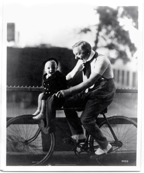 W.C. Fields and Baby Le Roy ride a bike.
