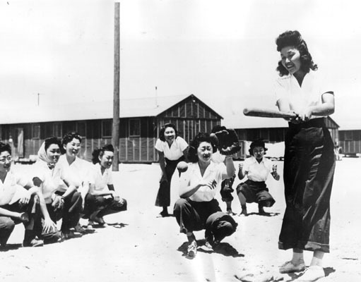 fuckyeahapihistory:  Girls' baseball team at Manzanar. July 17, 1942 Japanese-American prisoners made Manzanar more livable through recreation. They participated in sports, including baseball, football, and martial arts. Maye Noma, behind the plate, and Tomi Nagao, at bat, are pictured during a practice game between members of the Chick-a-dee softball team. The entire team was transplanted from Los Angeles to the War Relocation Authority Center at Manzanar.  Bet they would have whipped the Rockford Peaches.  Maybe not Tomi-chan.