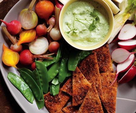Green Goddess Dip with Vegetables & Homemade Pita Chips  3 6-inch whole-wheat pitas 2 tsp canola oil Cumin Chili powder Kosher salt 2 cups chopped avocado (about 2) 1 cup nonfat Greek yogurt (such as Fage) or plain nonfat yogurt 1/4 cup fresh lemon juice 1/4 cup white wine vinegar 2/3 cup chopped fresh chives, divided 1/2 cup chopped fresh parsley 7 cups assorted fresh vegetables, raw or lightly steamed (e.g., beet slices, baby carrots, sliced fennel, julienned jicama, snow peas) 1 Preheat oven to 350°F. Cut each pita into 8 wedges. Brush with oil and sprinkle with ground cumin, chili powder, and kosher salt—all to taste. Bake for 8 minutes or until edges begin to brown. Turn off oven and let chips stand for 15 minutes or until crispy. 2 Meanwhile, put avocado, yogurt, lemon juice, vinegar, 1/3 cup chives, parsley, and salt to taste in a small food processor or blender and puree until creamy. Stir in most of remaining chives, reserving some to garnish dip. 3 To serve, spoon the dip into a small bowl and surround with vegetables and pita chips on a platter. Makes 20 servings. Per serving (2 Tbsp dip, 1/3 cup vegetables, and 1 chip): 77 cal, 3 g fat (<1 g sat), 11 g carbs, 135 mg sodium, 3 g fiber, 3 g protein  via Easy Meals and Easy Recipes | Women's Health Magazine