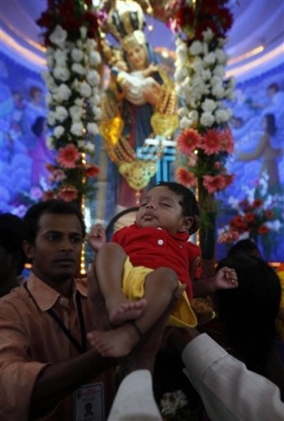 Indian Catholics hold up a child to receive a blessing at the shrine of  Our Lady of Health at the annual feast of Mary's birth in Hyderabad in  India on 8 September 2010. The feast of Mary's nativity is a big day for Indian Catholics, as it is  celebrated as a harvest festival and at many shrines newborns receive  blessings.Just like India's large Hindu population celebrates the  births of their many gods, Indian Catholics honour the day the Mother of  their God was born.