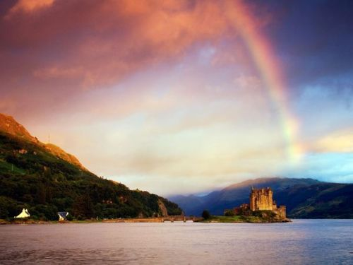 skysignal:  Eilean Donan Castle Photograph by Getty Images Widely  considered Scotland's most photographed site, Eilean Donan Castle  perches on an island at the meeting of three lochs in western Scotland.  The island's first castle was an early 13th-century fortification  against raiding Vikings, and it's been sacked and rebuilt several times.  The most recent facelift was completed in 1932.