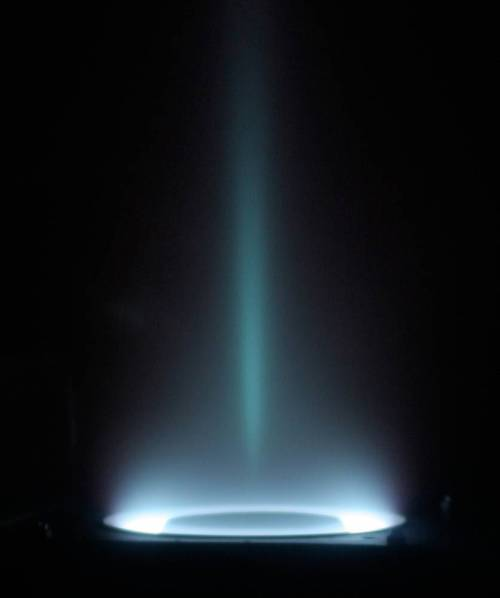 A picture of a Hall-effect thruster (plasma accelerator) plume. The Hall thruster, is an electric propulsion technology that uses magnetic and electric fields to ionize and accelerate propellant. In this image the plasma accelerator is operating on xenon propellant. (via freshphotons)