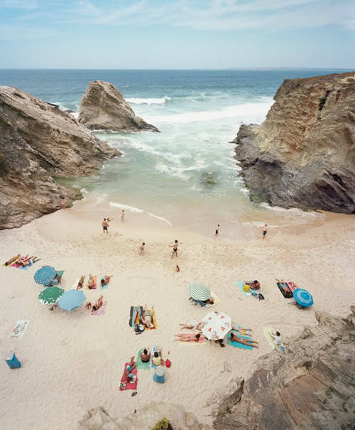 "The Christian Chaize image,  Praia Piquinia  Statement from 20X200:  """"The real voyage of discovery consists not in seeking new landscapes but in having new eyes."" —Marcel Proust  Five years ago, Portugal did present itself as a new landscape in my life - both literally and metaphorically. Since then, I have photographed exclusively along a very small stretch of its southern coastline. Returning to this specific place, I've sought out its nuances. In doing so, I have peeled back layers of how I see, and how I experience this magical environment. The results of my slight obsession have evolved into two distinct series. Here are two images from Praia Piquinia, a body of work focusing on a singular, secluded beach front in which all of the pictures are taken from essentially the same elevated angle. What the still life was for Morandi, this beach is for me. From a distance, I observe the variables: light, weather, time of day, the ebb and flow of the ocean, and the sunbathers, unaware, below my large format camera. The images are shot vertically, a departure from the traditional, horizontal format in landscape photography. It puts my subject matter in the form of a portrait - an ongoing record of this ethereal yet playful nook in nature over the minutes, the days, the years. Ultimately, I try to instill an element of time within these captured moments… visceral time, elastic from one image to another. And always, I seek to have new eyes."""