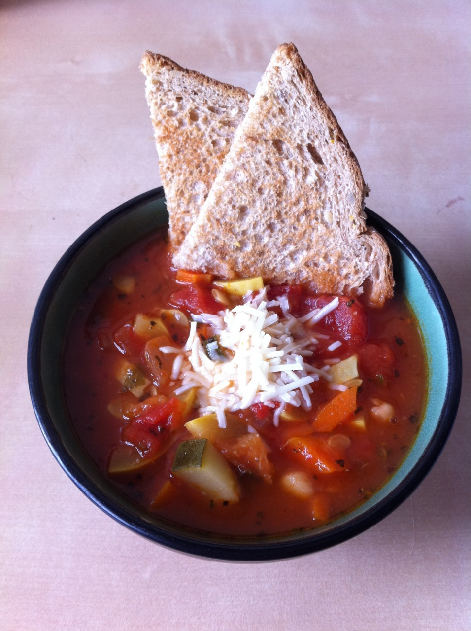Minestrone Soup (based on Uncle Bill's Vegetarian Minestrone) Makes 8-12 servings 6c water 1 can (28oz) crushed tomatoes (low sodium) 1 can (28oz) diced tomatoes (low sodium) 1 can (16oz) great northern beans 3 large carrots, peeled and chopped 1c onion, chopped 1 zucchini, chopped 1 yellow (summer) squash, chopped 4 large cloves of garlic, diced finely or pressed 1 handful of baby spinach, chopped 2tbsp olive oil 1tsp oregano 1/2 tsp salt 1/4tsp black pepper 1c small shells pasta, cooked Possible garnishes: Upton's Italian Sausage seitan, warm crusty bread, shredded parmesan cheese In a large stock pot, saute carrots, onion, zucchini, squash, and garlic with 1/2 of the olive oil for about 2 mins. Add beans, both cans of tomatoes, water, spices, the remaining oil, and spinach cook over medium-high heat until it comes to a boil. Reduce heat to medium and cover. Cook until the vegetables are tender, approximately 15-25mins. Serve over pasta. Freezing instructions: If freezing, do not add the pasta to the soup.