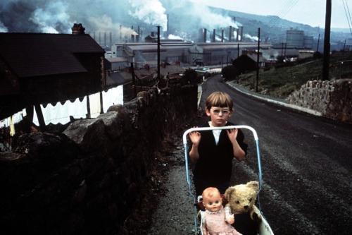 Bruce Davidson, South Wales, 1965 Last month I posted this Bruce Davidson shot, but it was black and white. At first I thought maybe somebody removed the color, but look at the boy's right hand, his leg and the overall frame. It's possible the other version was also color, or Davidson was using two cameras. I wasn't aware Davidson used color before the 1980 Subway series, and I'd love to see more from this period. I can't decide which version I like better; but the dense contrasty color, somewhat underexposed, really gives the feeling of sootiness and the boy's face and his pink doll are lost in the middle of it. Which version do you prefer?
