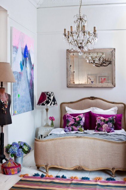 A gorgeous upholstered bed… stunning chandelier… unreal art… and floral accents…. Dream worthy!