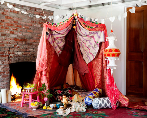 likeitseasy:  DIY VALENTINE'S DAY FORT; Materials; about 5 sheets, sarongs and/or large pieces of fabric a few blankets one pole (we used an old shower rod, but a broom stick would do); size will vary based on how large/small you'd like the fort to be 4 screw hooks 1 spool of twine 4 large safety pins 1 newspaper pom-poms fishing line lots of pillows tape measure scissors hole punch needle Instructions; For the Fort; 1. Measure the length of the pole. Decide where you'd like to build the fort, and screw two screw-hooks into the ceiling the same distance apart as the two ends of the pole. 2. Cut two, 3-foot long pieces of twine. Tie each piece of twine onto either end of the pole, and tie the other ends of the twine onto the screw hooks.   3. Start with the heaviest sheet, and begin to layer the sheets and fabrics over the pole. that will help maintain a more tent-like shape at the end. Once all the sheets are on the pole, measure about 2-feet down from the pole in front, and hook one safety pin through all of the sheets. Do the same on the parallel side. 4. Cut two pieces of twine about 3-feet long and tie one piece to each of the two safety pins. Screw the remaining two hooks into the ceiling about 2 feet from the pole on either side. (Actual distances will vary depending on how large you make the fort.) 5. Tie the two pieces of twine that are attached to the safety pins onto the two empty screw hooks in the ceiling. 6. Fill the inside will pillows and blankets for extra coziness; add chocolates, champagne and whatever else you fancy! For the Newspaper Heart Garland; 1. Fold newspaper in half and cut out a half-heart shape from the fold. 2. Keep the hearts folded and punch one hole into the center of the folded heart so that once the heart is open, there are two holes. 3. Weave the twine through the holes in the paper hearts to complete the garland.