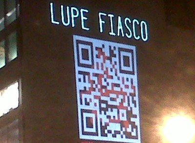 "PSFK » Lupe Fiasco Tags Union Square [Pic] ""As part of a promotion for the new Lupe Fiasco album Lasers,  a massive QR code is being projected in New York City's Union Square. The promotion works in two ways. The code requires users to scan it with RedLaser,  a technology that enables fast, clean reads of QR codes, evidently at  some distance. To Lupe Fiasco's benefit, scanning the code is a  pre-order for his new album with the bonus of additional content."""