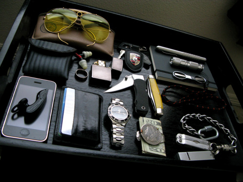 everydaycarry:  submitted by dkrysis  Hey man, Just wanted to thank you for giving me something to do while the wife watches must see TV. Here are some things I've collected over the years. Most of it is pretty old. Thanks again for putting in the time. Old Ray-Ban Bullet Hole Glasses Car Key w/Key Chain LED Notebook Stainless Steel Pen Stainless AA Flashlight w/Breakaway Neck Lanyard Slip n Snip Scissors Etymotic Headphones Zippo Chick Magnet (wedding ring) SOG Knife K-Bar Knife iphone  Credit Card Holder Omega Seamaster 1st Gen 1883 Silver Dollar Money Clip Screw Lock Carabiner w/Chain and Quick Disconnect Key Chain Leatherman Micra 2 gig Thumbdrive  Editor's Note: This pic makes me think I need to step up my EDC storage game… Nice collection! I especially like that Seamaster and Micra + Chain. Thanks for sharing~