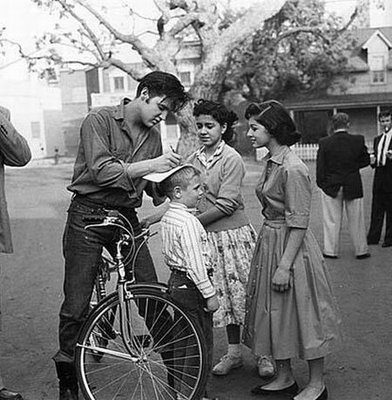 Elvis Presley rides a bike. And signs autographs on a kid's head.