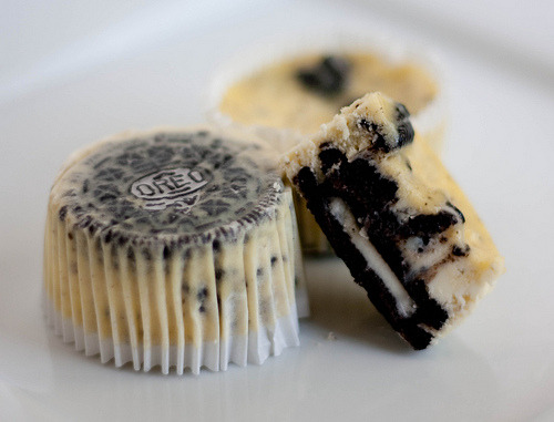 smilingfork:  Cookies & Cream Cheesecake Cupcakes Difficulty: ★☆☆☆☆ (Easy) Yield: 30  Ingredients: 42 cream-filled sandwich cookies, such as Oreos, 30 left whole, and 12 coarsely chopped 2 pounds cream cheese, room temperature 1 cup sugar 1 tsp vanilla extract 4 large eggs, room temperature, lightly beaten 1 cup sour cream Pinch of salt Directions: 1. Preheat oven to 275 degrees. Line standard muffin tins with paper liners. Place 1 whole cookie in the bottom of each lined cup.2. With an electric mixer on medium high speed, beat cream cheese until smooth, scraping down sides of bowl as needed. Gradually add sugar, and beat until combined. Beat in vanilla.3. Drizzle in eggs, a bit at a time, beating to combine and scraping down the sides of the bowl as needed. Beat in sour cream and salt. Stir in chopped cookies by hand.4. Divide batter evenly among cookie-lined cups, filling each almost to the top. Bake, rotating pan halfway through, until filling is set, about 22 minutes. Transfer to wire racks to cool completely. Refrigerate at least 4 hours (or up to overnight). Remove from tins just before serving.
