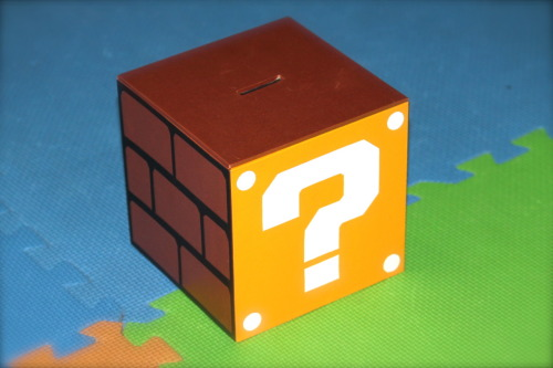 "Our loot bag — a custom made 6"" cube that can be a coin bank or container for a child's treasures.  Inside, we placed white paper crepe confetti that hid a custom-made plush Star, a customized Power-Up mushroom pouch (thanks to www.coolpartyblog.com for the original template) and chocolate coins"