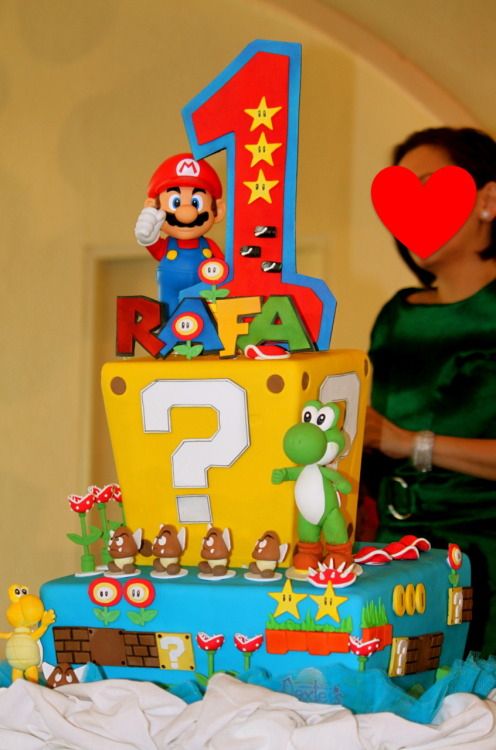 Super Mario Bros themed party One of the two Fondant cakes we had specially made for the event.   With the exception of the big Mario toy figure, everything else were hand made sugar sculptures.  My wife and I sat down with the owner of Dexter's Bakeshop to show photo references, actual Mario toys and character key chains (to use as reference for character proportions).   I guess we inspired Chef Raymond enough to go out of his way in making his first Mario Bros-themed fondant cake simply amazing.  I love the asymmetrical design of the cakes; it gave the cake the fluid movement that fits nicely with the video game theme. My only complaint was that the same sugar characters were lined up together rather than spreading/mixing them all other the cake for better effect.  I didn't want to risk ruining the cake by moving them around so that's what the guests saw.
