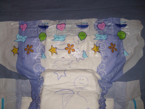 These are one of my most favorite AB diapers to wear: CUSHIES They are the first adult baby diaper to be fully all around printed with babyish prints. The sides are colored in wavy blueish purple with white spirals and the center is white with blue outlines of stars and hearts and such. There is a landing zone in the top with colorful hearts, stars, sailboats and clouds for the ONE TAPE on each side that is 3 Inches wide to complete the Baby feel. These diapers are SUPER comfy and are decently thick. They also make aLOT of noise when you walk in them which is a total plus for me because I love the crinkly diaper sound. They are plastic backed just like the classic diapers from back in the day and are perfect for playing in because those tapes are TOUGH and never come off unless you pull them off. These diapers are really fun to wet and don't become too bulky when you wet them which I think is just fine. You definitely want to flaunt these diapers, these are all about appearance! The leg cuffs make this diaper look oh so cute from behind and nearly complete the baby diaper look and feel. What I would Add: I would like it more if it had a waistband because in my baby past, my diapers had waistbands and I miss that :P. Aside from that this diaper is perfect for Adult Babies AND Diaper Lovers (although some people would prefer them thicker lol ) Where you can get them: AB Universe Cushies The larges come with a darker shade of purple on the sides and are slightly taller than the mediums. You can also add a Baby Fresh Scent that reminds you of those good ol' Pampers days :)
