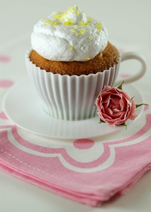 Passionfruit Meringue Cupcakes cupcake batter - 1 ¼ cup flour - 3/4 teaspoon baking powder - 1/4 teaspoon salt - 2/3 cup milk - 5 tablespoons unsalted butter, cut in pieces - 2 large eggs - 1 large egg yolk - 1 ¼ cup sugar - 1 teaspoon vanilla extract - 1/4 teaspoon almond extract - about 1 cup passion fruit curd  1. Pre-heat oven to 350°F.  Line a 12 cup cupcake mold with paper liners. 2. Sift flour, baking powder, and salt into a bowl. Set aside.Heat milk and butter in a small saucepan until hot. 3. In another bowl, with an electric mixer beat the eggs, yolk, and  sugar until thickened. Add vanilla and almond extracts. Incorporate the  flour mixture, and then slowly mix in the hot milk. Mix until the batter  is smooth, but don't over beat. Divide the batter evenly among the 12  cupcake liners. 4. Bake until the tops are firm and a toothpick inserted in the  center comes out clean, about 20 minutes.  Remove the cupcakes from the  pan, and let cool on a wire rack. 5. Pipe the passion fruit curd filling right into the cupcakes with a long piping tip. Alternatively, cut out a cone shaped piece from the cupcakes to make a  hole for the filling. Cut the lower part of the cone, leaving you with a  circular lid. Spoon the filling inside the holes, and replace circular  lid on top of the filling. 6. Prepare the 7 minute frosting according to the directions below.  Frost the cupcakes and dust some fun sprinkles over the top. Share and  enjoy!  passion fruit curd - 1 cup sugar - 1/2 cup passion fruit concentrate - 6 large egg yolks - 4 tablespoons unsalted butter, diced  1. In a medium saucepan, place the sugar, passion fruit concentrate  and egg yolks. Cook over medium heat, whisking constantly until the  mixture thickens. This should take about 15 minutes. Turn heat off, and  add the butter pieces one by one until all the butter is incorporated.  Let cool and refrigerate until ready to use it. Makes about 2 cups.  7 minute frosting - 1 cup plus 1tablespoon sugar - 1/2 cup water - 1 teaspoon light corn syrup - 4 large egg whites, at room temperature  1. In a small saucepan, place 1 cup of the sugar, water and corn  syrup. Place a candy thermometer on the side of the pan. Bring mixture  to a boil over medium heat without stirring until it reaches 230°F. 2. While the mixture is coming up to 235°F, in the bowl of a standing  mixer, beat the egg whites on medium speed until soft peaks form. Add  in the remaining 1 tablespoon sugar. 3. When the sugar syrup reaches 230°F, slowly pour the syrup on the  inside side of the bowl while beating the egg whites on low. Once you  have added all the syrup, change the speed to high, and beat for 7  minutes until stiff peaks form. Use immediately.  Recipe for cake from Cupcakes by Elinor Klivans.Recipe for passion fruit curdand 7 minute frosting from Martha Stewart.  tips + tricks - You can make the passion fruit curd up to three days in advance. - You can make the cupcakes and fill them up to one day in advance. - If you have a long piping tip like this one and piping bags you can just fill the cupcakes by inserting the point  of the tip in the middle of the cupcake and squeezing the filling into  it until you see the cupcake expand slightly. If you don't have a long  piping tip, then just cut out cone shaped pieces from the middle top of  the cupcake and spoon the filling into the holes - Decorate your cupcake platters with simple things such as fresh flowers and colorful paper napkins. - Silicone teacups are a fun and different presentation, and reusable. - Don't make the 7 minute frosting on rainy or very humid days, it won't get fluffy and won't set as it should.