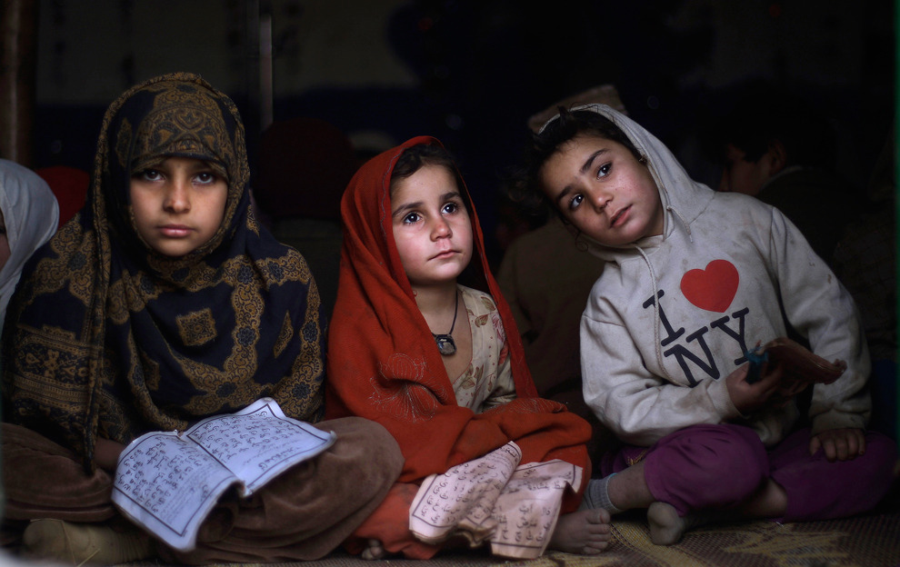 Two Afghan refugee sisters and a Pakistani girl  attend a daily class to learn how to read verses of the Koran, at a  mosque in a slum area on the outskirts of Islamabad. (Muhammed  Muheisen/Associated Press)