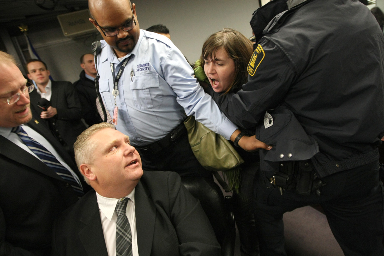 "Arrests made as OCAP protest shuts down Toronto budget meeting  Protesters with the Ontario Coalition Against Poverty disrupted a meeting of Toronto's budget committee, demanding that Mayor Rob Ford reverse cuts they say target the poor.Shortly after 10 a.m., Heather Schofield entered committee room demanding the attention of councillors who had been listening to a presentation about the city's financial future. Budget Chief Mike Del Grande quickly recessed the meeting, as the procession of activists neared.""We're here because the proposed cuts that they're making are devastating,"" Heather Schofield told reporters after. ""This is a crisis, we're not talking about can we politely please ask sir for a little more food. People are dying on the streets of Toronto, that's what we're talking about. And if you want to tell us to stand in a queue and wait and speak politely, that's bogus."" (Photo: Brett Gundlock/National Post)  Check out our full visual archive."