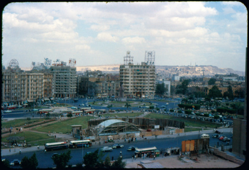 "Cairo, United Arab Republic, April or May 1963 The view is a snapshot of three competing visions for Egypt. The distant mosque represents the controversial legacy of a dynasty that had ruled until 1952; the Turkish patriarch Mohammed Ali Pasha is sometimes honoured as the ""father of modern Egypt"" because he opened the country culturally and institutionally to the West. His grandson, Khedive Ismail, built the square that temporarily bore his name to a French design. He is perhaps better known for the Suez Canal, which ran Egypt into irreparable debt to European creditors, tipping the country into the arms of British imperial control. Nasser's UAR was another push toward modernization, a heavily subsidized transit system turning Midan Al-Tahrir into a commuter hub for a growing population of urban workers; the bus depot is this period's triumphal arch."