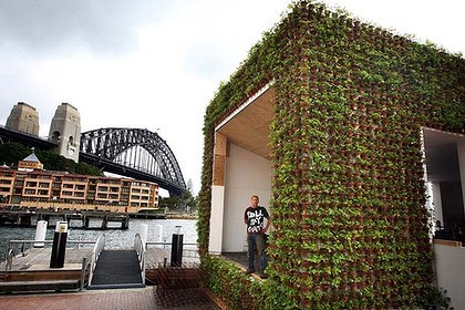 "Joost Bakker's new temporary cafe at The Rocks [in Sydney, Australia] may be one of the greenest buildings on Earth. Named ""Greenhouse by Joost"", everything about the installation artist's cafe has been created using inexpensive recycled or recyclable materials down to glasses made from sawn-off beer bottles and uniforms sourced from the Salvation Army and election campaigns past. Bakker stands inside a shipping container, a row of jam jar lightbulbs illuminating his face as he explains the incredible structure around him. Furniture is made from old irrigation pipes and leather treated with vegetable dye, rubber floor tiles arranged in a herringbone pattern were once conveyer belts. In the dining area a flattened wine bottle is used as a cheese tray - the neck now a handle. ""We … set out to build a place that was completely recyclable - made from steel, not wood, and had straw in the floor, walls and ceiling,"" Bakker said. (via Waste not, want not, an artful eco-cafe sets the scene green - The Sydney Morning Herald)  The pop-up Greenhouse, built in three weeks and based on earlier installations in Melbourne and Perth, will, according to this post on Joost's Web site, ""operate for eight weeks in Sydney before continuing its tour in Milan. The travelling restaurant will then continue on to a number of other European cities."" Each city's menu is based on what grows locally (and on the building's rooftop garden) and is in season."