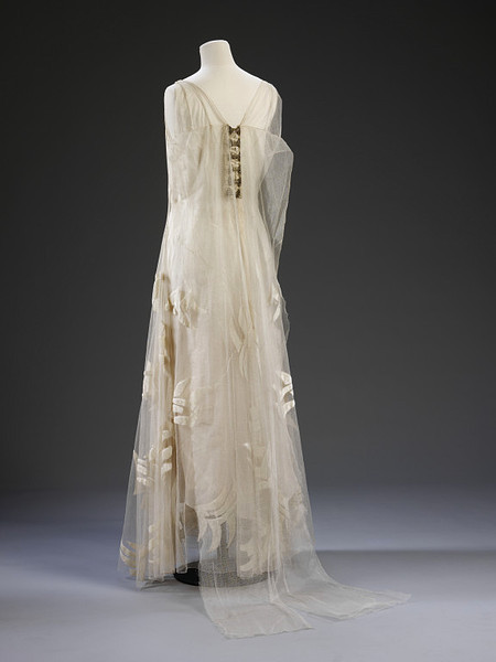 Vionnet | Evening Gown | c. 1935 In Vionnet's hands, finishing details such as hems, seams and applied decoration are executed with precision and finesse. This dress was designed by Vionnet in 1935. By this year, Vionnet had operated her own couture house for 23 years and had worked for nearly 50 years in the dressmaking and couture trades. The dress is crafted from organza and fine tulle. Its delicacy is underlined by the scattering of appliquéd velvet swallow motifs across the skirt.