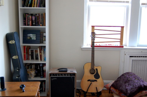 a corner of my living room and a few of my favorite things: two of my guitars, my books, and my father's amp.