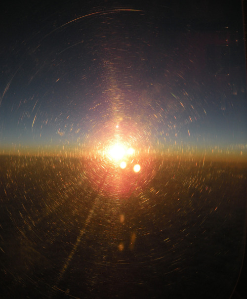 Obsessively took a hundred photos of the sun rising through the thick window of a plane at 6 AM. The spirals created by the reflection through multiple sheets of distorting plastic have a spider web effect that had my mind going…