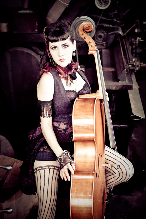 This is the lovely Ashia Grzesik, solo artists and member of Vagabond Opera and Portland Cello Project.  She creates songs with elements of cabaret, folk, pop, and dark Americana. Her songs and writing reflect longing for her Slavic roots with Chopineasque and gypsy musings and the blues, rock, and open harmonies of the New World. Submitted by Dr. Xander Gerrymander  Wow, she's quite the steampunk beauty!