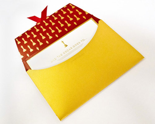 "A Redesign for the Oscars Envelope To honor the 70th anniversary of the Academy Awards, designer Marc Friedland brings out the bling with iridescent gold paper for his ""iconic"" makeover of the ordinary white envelope and plain announcement cards.  ""…The  outside of the envelope and flap is an Art Deco-inspired satin gold  foil frame with  an ecru inset panel bearing the name of the award  category in a rich charcoal  ink. The envelope will contain a   heavyweight ecru card featuring gold foil accents and a gold   leaf-embossed Oscar statuette along with the phrase, ""And the Oscar goes   to….""  The winner's name will  be printed in charcoal ink and mounted  onto a matching, red lacquer  hand-wrapped frame…"" —press release from The Academy   We look forward to seeing these designs on the screen on ABC this upcoming Sunday, February 27, 2011 and appreciate the extra attention to detail this year. (photo credit: Patrick Prather / ©A.M.P.A.S., video via LAT via AP)"
