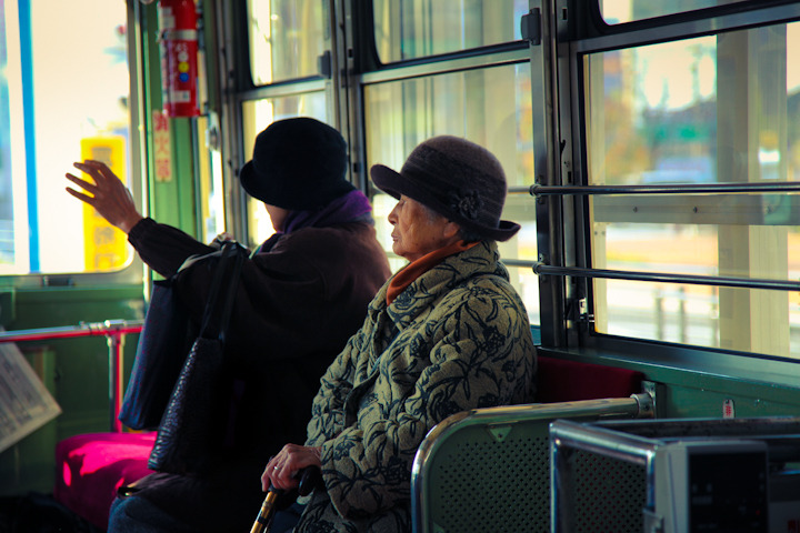"PEOPLE OF JAPAN 25 - ""ADORABLE HAT LADIES ON TROLLEY"" After I took this picture I told Vicki that she needed to get a cute little hat. She politely replied, ""that's not necessary because I can steal your cozy winter cap whenever I want""."