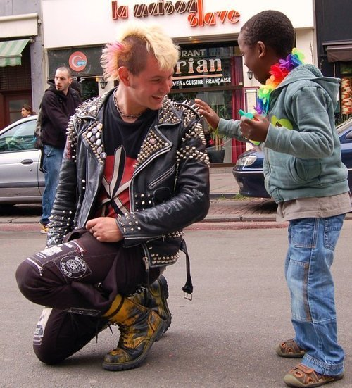 mrgolightly: A punk stops during a gay pride parade to allow a mesmerized child to touch his jacket spikes.
