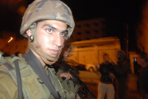 Soldiers raid a Palestinian home in Hebron. September 2009, soldiers use the tactic of collective punishment to squash any potential sign of action among the youth. For the crime of a boy throwing a few stones at a checkpoint, an entire family's home was invaded and ransacked. A boy was beaten for being at the wrong place at the wrong time and an old man was attacked by a soldier pushing the barrel of a rifle onto his chest while he tried to defend his home. International observers who arrived were shoved by soldiers and received threats of death and rape.