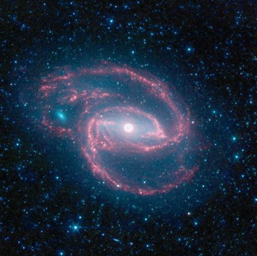 app1ejuice:  This galaxy, called NGC 1097, is located 50 million light-years from Earth. with an eye-like object at its center harbors a hidden black hole. The ring around the black hole is bursting with new star formation. An inflow of material toward the central bar of the galaxy is causing the ring to light up with new stars.. The galaxy's red spiral arms and the swirling spokes seen between the arms show dust heated by newborn stars. Older populations of stars scattered through the galaxy are blue. The fuzzy blue dot to the left, which appears to fit snuggly between the arms, is a companion galaxy. (click image for full article)