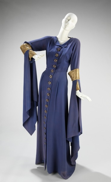 "Lanvin dress in ""Lanvin blue"", fall-winter 1934-35  This particular shade of blue is known as ""Lanvin blue.""  The shade was  one of the many designer colors which Lanvin had produced in her dye  factory in Nanterre, France.  The color could not be reproduced and  therefore was never subjected to reproduction as was many of the  designer garments in this period where design theft was rampant.  As  with many of Lanvin's creations, this garment shows historical  representation.  Its loose style and sleeve design are directly  mimicking of the houppelande worn by men and women in the 14th and 15th  centuries."