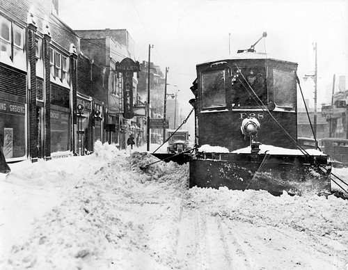 """A streetcar equipped with a snowplow clears a Chicago street in 1939."""
