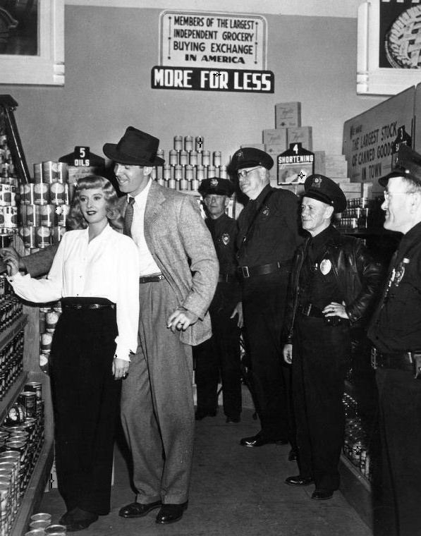 oldhollywood:  Barbara Stanwyck & Fred MacMurray on the set of Double Indemnity (1944, dir. Billy Wilder) Wartime food shortages meant that security guards were posted to protect the real cans of food in the grocery store from sticky-fingered cast & crew members. Despite this, the aggrieved store owner reported to the LA Times that some scoundrel had managed to pinch a can of peaches & four bars of laundry soap.  (via)