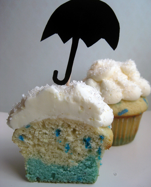 "Rainy day cupcakes! I couldn't bake real rain into a cupcake, but some blue food coloring and sprinkles almost do the trick! To make your own, just add a couple drops of blue food coloring or food gel to 1/3 of your favorite vanilla cake batter. Scoop a tablespoon of it into the bottom of your paper lined cupcake tins to make the ""puddle."" Next, add a few tablespoons of blue jimmies sprinkles to the remaining (undyed) batter to make the raindrops. Add a couple tablespoons of that to the cupcake tins. Then bake! Finish 'em off with a ""cloud"" of white vanilla buttercream—suddenly your rainy, cloudy day becomes a delicious treat! (You know what goes really well with rainy day cupcakes? DOUBLE RAINBOW CUPCAKES! All the way!) My cookbook, Bake It in a Cupcake: 50 Treats With a Surprise Inside, is available for pre-order NOW at: Amazon.com, Barnes & Noble, and Indiebound.com!"
